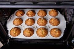 De wortel wordt cupcakes gebakken in een hete oven stock afbeeldingen