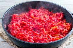 De wortelen, de bieten en de ui in een pan worden geroosterd op het fornuis Ingrediënten voor borsjt stock foto