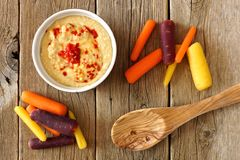De wortelen van de babyregenboog met hummus, luchtmening op rustiek hout Royalty-vrije Stock Afbeelding