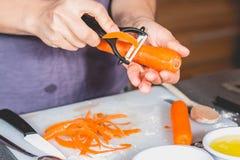 De wortelen van de kokschil met een ceramisch mes Stock Afbeelding