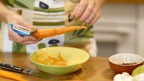 De wortelen van de meisjesschil voor salades stock videobeelden