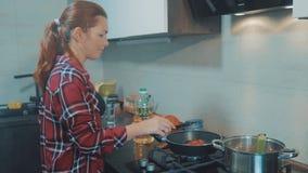 De wortelen van het meisjesgebraden gerecht in de pan vrouwenkoks in de keuken die thuis het roosteren doen Portret van jonge vro stock videobeelden