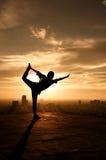 De yoga stelt bij de bouw bij suset stock foto's