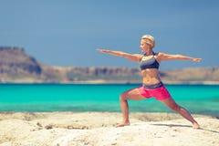 De yoga stelt, paste vrouwenoefening op strand Royalty-vrije Stock Afbeeldingen