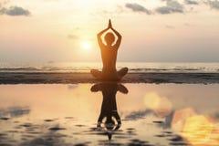 De yoga van de silhouetvrouw op het strand bij zonsondergang ontspan stock foto