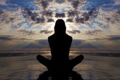 De yoga van de zonsondergang stelt op het strand. Stock Foto's