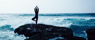 De yoga van de vrouwenpraktijk bij de kust stock afbeeldingen