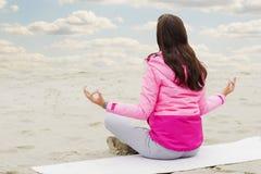De yoga van vrouwenpraktijken en mediteert in de lotusbloempositie inzake het strand stock fotografie