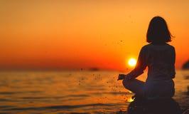 De yoga van vrouwenpraktijken en mediteert in lotusbloempositie inzake zonsondergang B Stock Fotografie