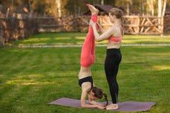 De yogainstructeur helpt beginner om asanaoefeningen openlucht te maken stock fotografie