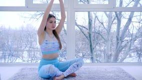 De yogaklasse, mooi meisje mediteert thuis en neemt diepe adem stock videobeelden