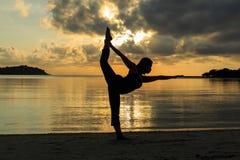 De yogameisje van het silhouet bij zonsopgang op het strand Stock Afbeeldingen