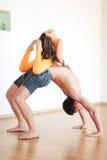 De yogapraktijk, een mens bevindt zich op de brug, is een klein meisje Stock Afbeeldingen
