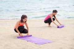 De yogastudent houdt yogamat na afwerking de openluchtstrandklasse, heelt stock foto