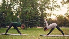 De yogastudent oefent in openlucht met instructeur het uitrekken zich benen en rug uit die vooruit status op matten op groen buig stock videobeelden