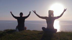 De yogatraining, atletisch paar op land tijdens zonsondergang zit in lotusbloempositie bovenop berg bekijkend het overzees, menin stock footage
