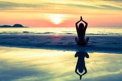 De yogavrouw van de silhouetmeditatie van zonsondergangoverzees Royalty-vrije Stock Foto