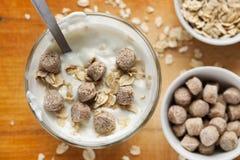 De yoghurt in glas met haver schilfert en zemelen daarin, selectieve nadruk, hoogste mening af royalty-vrije stock foto's
