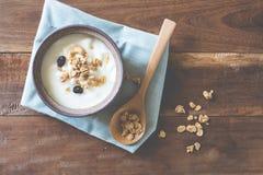 De yoghurt versiert met graangewas in een kom op woodtable Stock Afbeelding