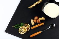 De yoghurtplaat, muntbladeren, snijdt van citroen, tarwe, noten, stokken van kaneel en een lepel op een zwarte schalieraad, op ee Stock Afbeeldingen