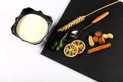De yoghurtplaat, muntbladeren, snijdt van citroen, tarwe, noten, stokken van kaneel en een lepel op een zwarte schalieraad, op ee Stock Foto