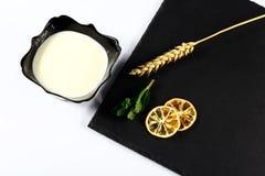 De yoghurtplaat, muntbladeren, snijdt van citroen, tarwe, op een zwarte schalieraad, op een witte hoogste mening als achtergrond, Royalty-vrije Stock Foto's