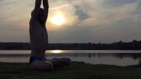 De yogimens zit in een lotusbloem en heft zijn handen bij zonsondergang in slo-mo op stock video