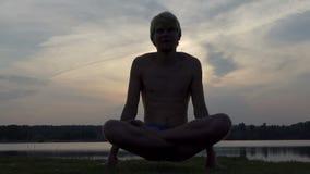 De yogimens zit in een lotusbloem en heft zijn lichaam bij zonsondergang in slo-mo op stock videobeelden
