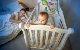 De Yougnmoeder viel in slaap terwijl haar slapeloze baby die zich in wieg bevinden stock fotografie