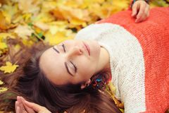 De Youndvrouw ontspant met gesloten ogen in de herfstpark stock foto's