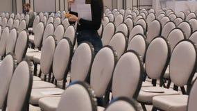 De zaal van de conferentie Rijen van grijze stoelen Een vrouwenaantallen de zetels voor speciale gasten stock footage
