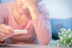 De zachte nadruk op droevige vrouwenhand houdt het zwangere teststootkussen na zaag het negatieve testresultaat Royalty-vrije Stock Foto's