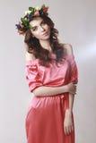 De zachte romantische verschijning van het meisje met een kroon van rozen op haar hoofd en een roze kleden zich Blij spring heel  stock fotografie