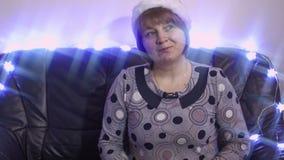 De zachte vrouw op middelbare leeftijd met Vader Christmas GLB glimlacht en danst stock footage