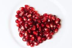 De zaden van de granaatappel op witte achtergrond De vorm van het hart stock afbeeldingen
