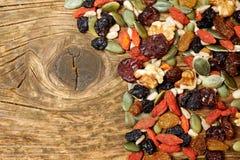 De zaden van mengelingsnoten en droge vruchten, op een houten lijst stock afbeelding
