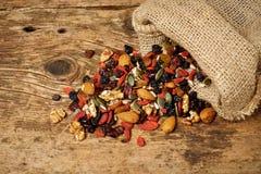 De zaden van mengelingsnoten en droge vruchten, op een houten lijst stock foto's