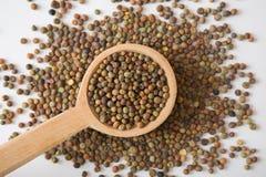 De zaden van peulvruchtroveja op een houten lepel Stock Fotografie