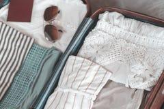 De zak van de open reiziger met kleding, toebehoren en paspoort, reis en vakantiesconcept De voorbereidingsconcept van de reiskof stock foto's