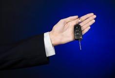De zaken en de gift als thema hebben: de autoverkoper in een zwart kostuum houdt de sleutels aan een nieuwe auto op een donkerbla Royalty-vrije Stock Foto's
