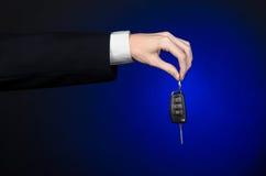 De zaken en de gift als thema hebben: de autoverkoper in een zwart kostuum houdt de sleutels aan een nieuwe auto op een donkerbla Stock Afbeelding