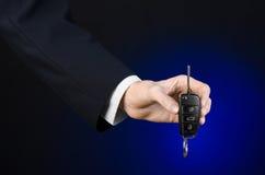 De zaken en de gift als thema hebben: de autoverkoper in een zwart kostuum houdt de sleutels aan een nieuwe auto op een donkerbla Royalty-vrije Stock Afbeeldingen