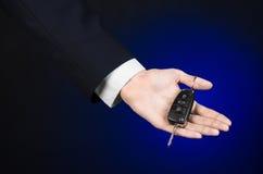 De zaken en de gift als thema hebben: de autoverkoper in een zwart kostuum houdt de sleutels aan een nieuwe auto op een donkerbla Stock Foto's