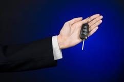 De zaken en de gift als thema hebben: de autoverkoper in een zwart kostuum houdt de sleutels aan een nieuwe auto op een donkerbla Stock Fotografie