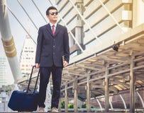 De zakenlieden die zonnebril dragen reizen met hun bagage stock afbeeldingen