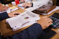 De zakenlieden gebruiken calculators en analyse bedrijfsgegevens en en grafiek financieel diagram die op de vergadering werken stock afbeeldingen
