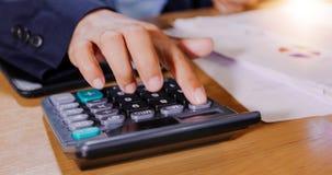 De zakenlieden gebruiken calculators en analyse bedrijfsgegevens en en grafiek financieel diagram die op de vergadering werken stock afbeelding