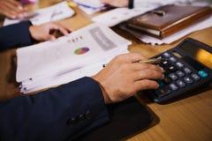 De zakenlieden gebruiken calculators en analyse bedrijfsgegevens en en grafiek financieel diagram die op de vergadering werken stock foto's