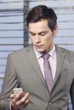 De zakenlieden in het bureau die op de cel letten telefoneren stock afbeeldingen