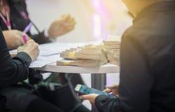 De zakenlieden ondertekenen financiële contracten en hebben geldpu stock foto's